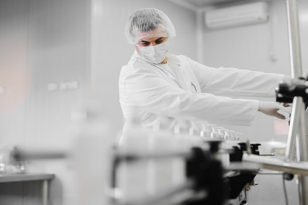 Picture of young man in sterile clothes controlling production line of cosmetic products. Standing in bright room and using control board..