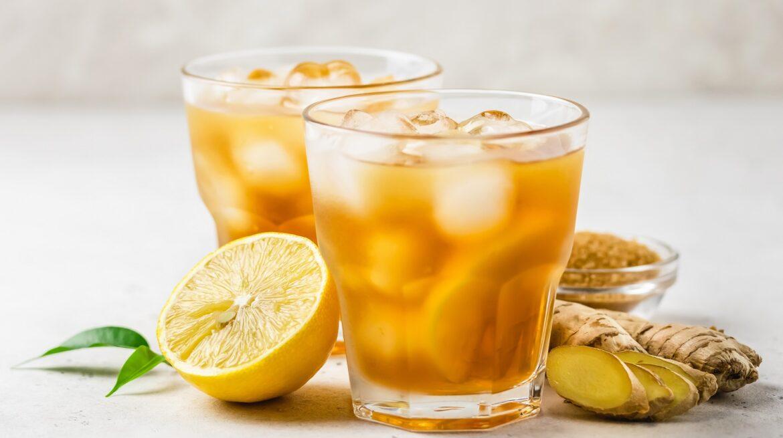 Fresh lemon honey iced ginger tea in glasses. Space for text.